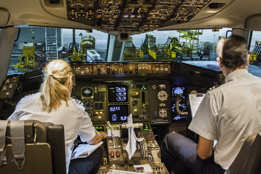 Female BA Pilot busy in the cockpit T5 LHR