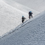 Climbers descending a snowy ridge
