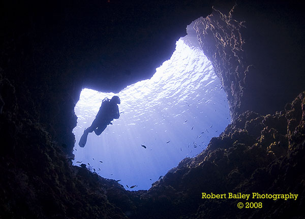 Diver in cave entrance at Capo Figari