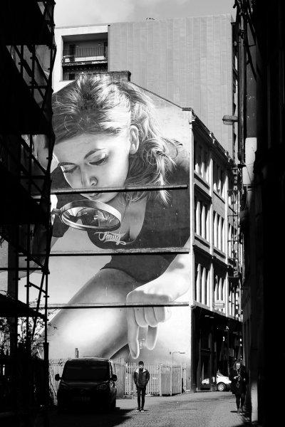 Pick me up... pedestrian walks past Glasgow street mural.