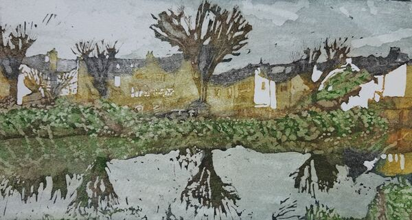 yellow brick houses, London plane trees and vegetation reflected in a river
