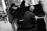 Piano player and audience at St Pancras station