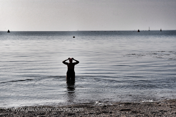 A swimmer on Plymouth Hoe foreshore prepares to head out to the breakwater