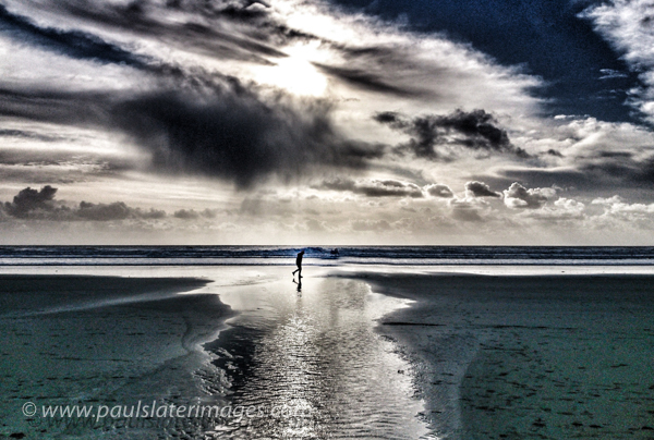 Solitary walker on the beach at Whitsand Bay, Cornwall.