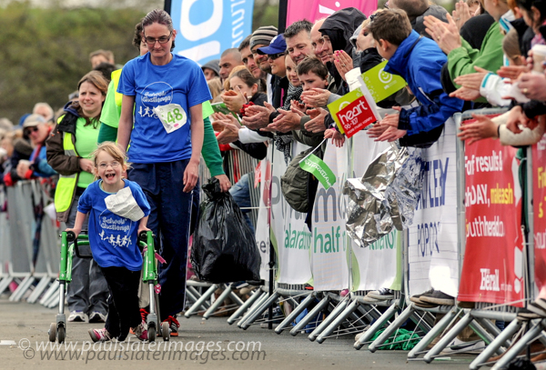 A young participant is encouraged by the crowds during the Children's event of the Plymouth Half Marathon.
