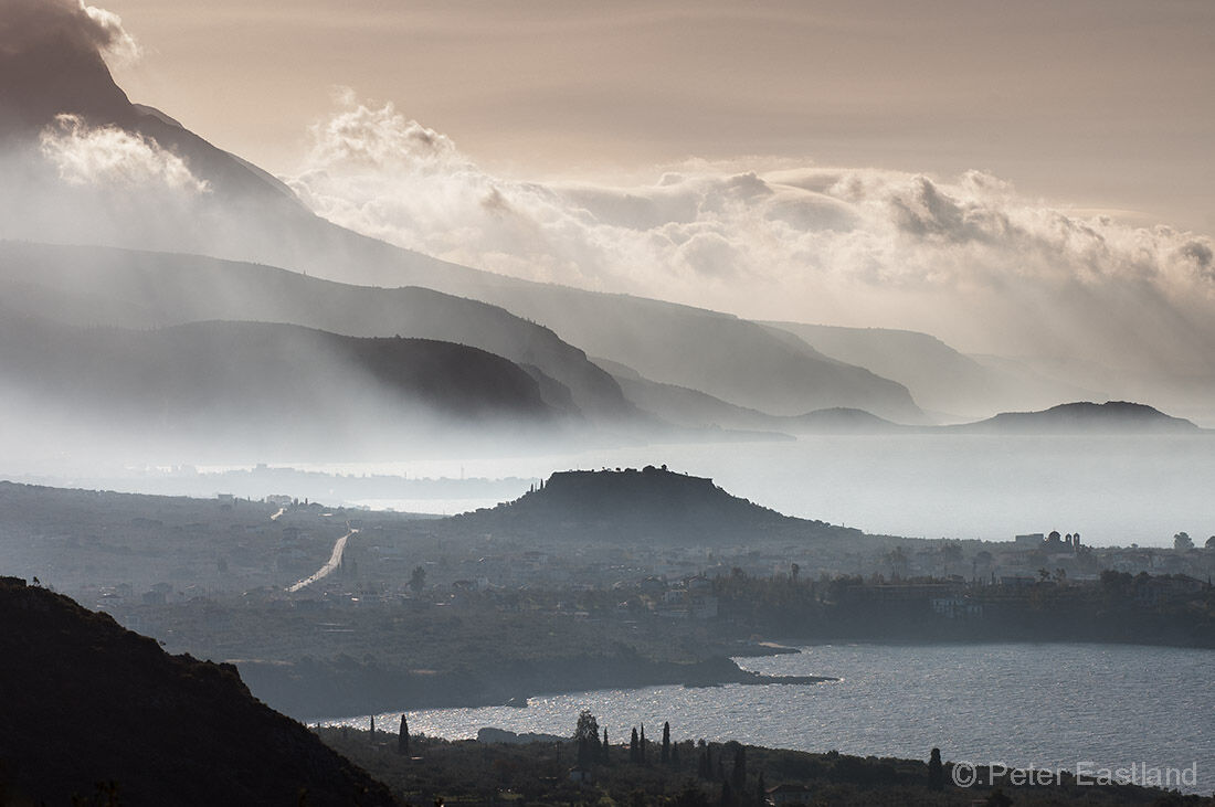 Looking south down the Messinian coast of the Outer Mani on a misty morning with the prominent mound of Stoupa's ancient acropolis in the middle distance.<BR><BR><BR><br><br>