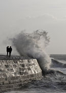 Stormy wave on The Cobb with couple, Lyme Regis, Dorset