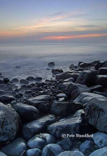 Rocky seashore at dusk, Llantwit Major, south Wales.
