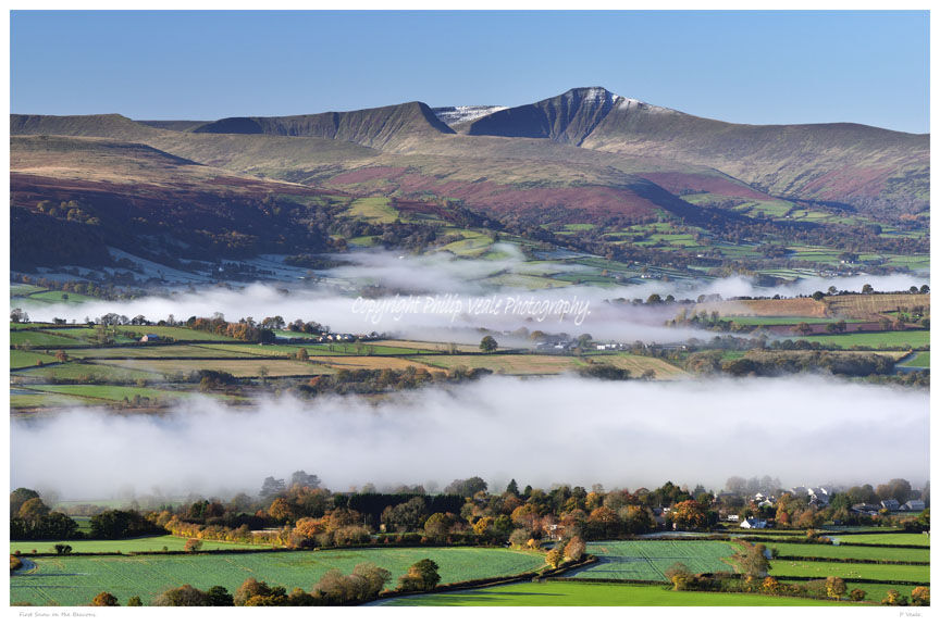 Llangorse Lake and the River Usk shrouded in mist with Pen y Fan and Corn Du in the Brecon Beacons showing the approach of winter with the first light dusting of snow on their peaks.