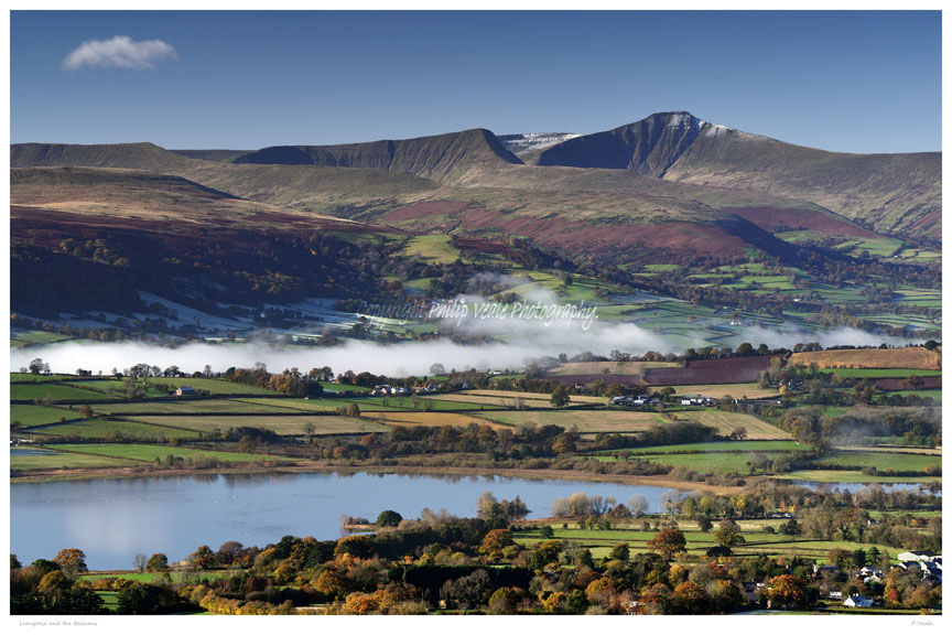 Brecon Beacons and Llangorse Lake in autumn with early morning mist drifting across the valley floor..