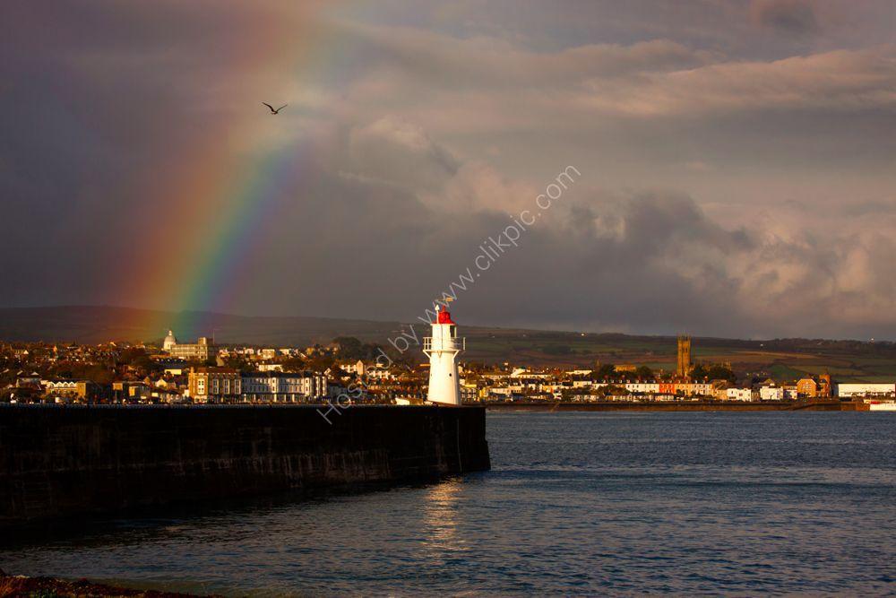 Rainbow over Newlyn harbour lighthouse and Penzance.