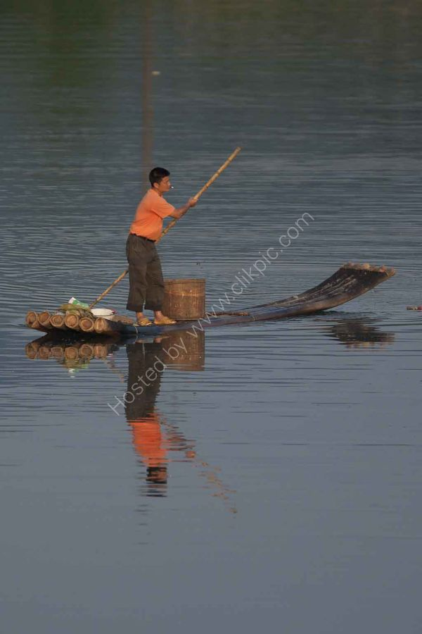 Chinese fisherman on a bamboo punt