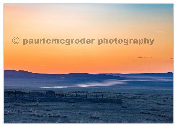 Car travelling through Gobi at sunset