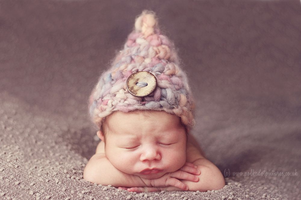 Newborn baby posed on front wearing pixie hat