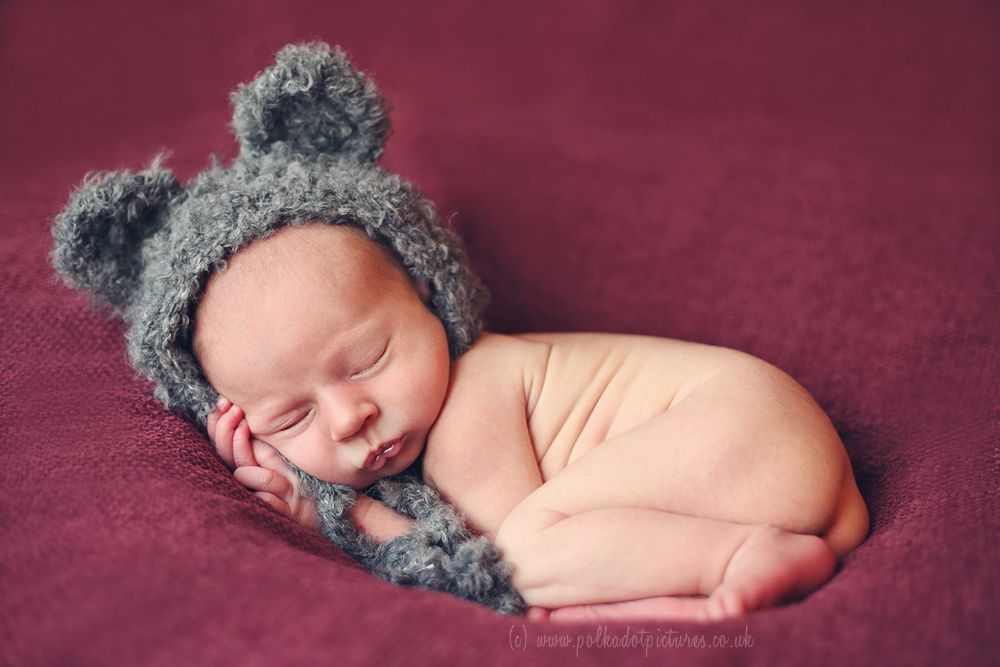 Newborn baby posed curled up wearing mouse hat