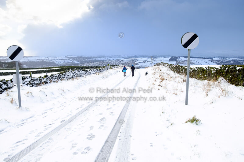 Couple with a dog walking on the hills above Keighley West Yorkshire UK
