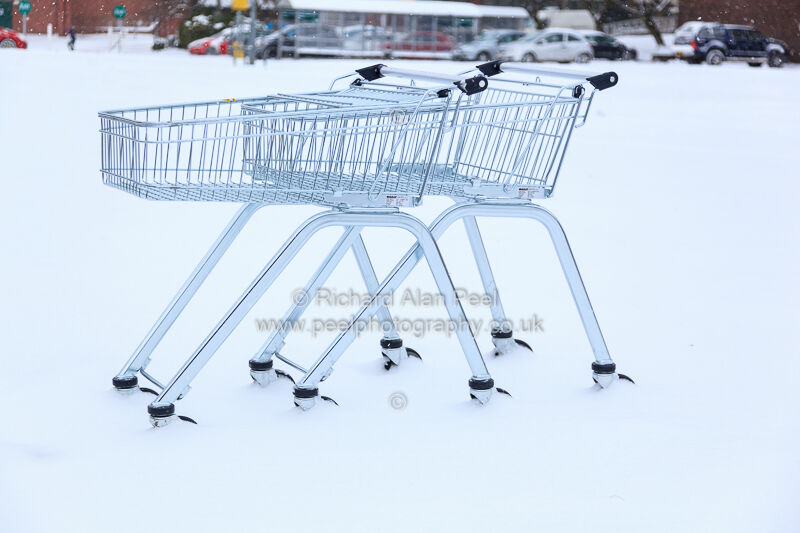 Supermarket trolleys snow covered car park Keighley West Yorkshire England UK