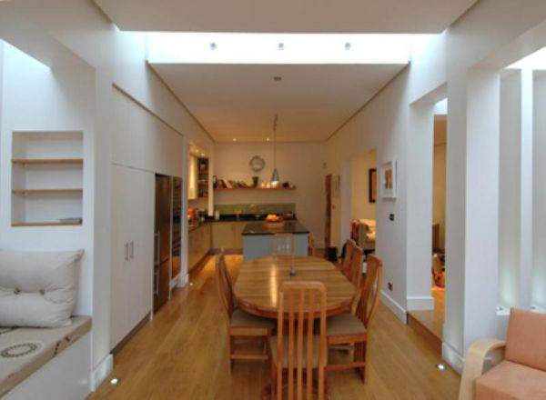 View from dining area towards kitchen. Note the ceiling edge details and integration of natural light.