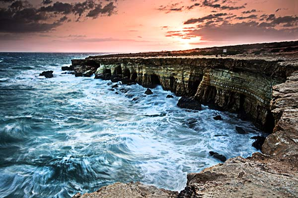 This is an image of a sea cove and caves in one of Cyprus National Parks at sunset and the sea raging