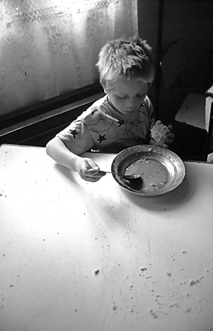 Bacau, Romania. 1994. A child eats soup and bread at an orphanage in this northern city.