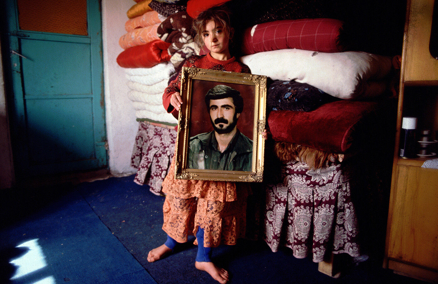 Cizre, south-east Turkey. March 1993. A Kurdish girl holds a portrait of her brother, a fighter with the Kurdistan Workers' Party, PKK, who was killed in combat with the Turkish military.