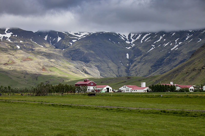 Farm below cloudy mountains