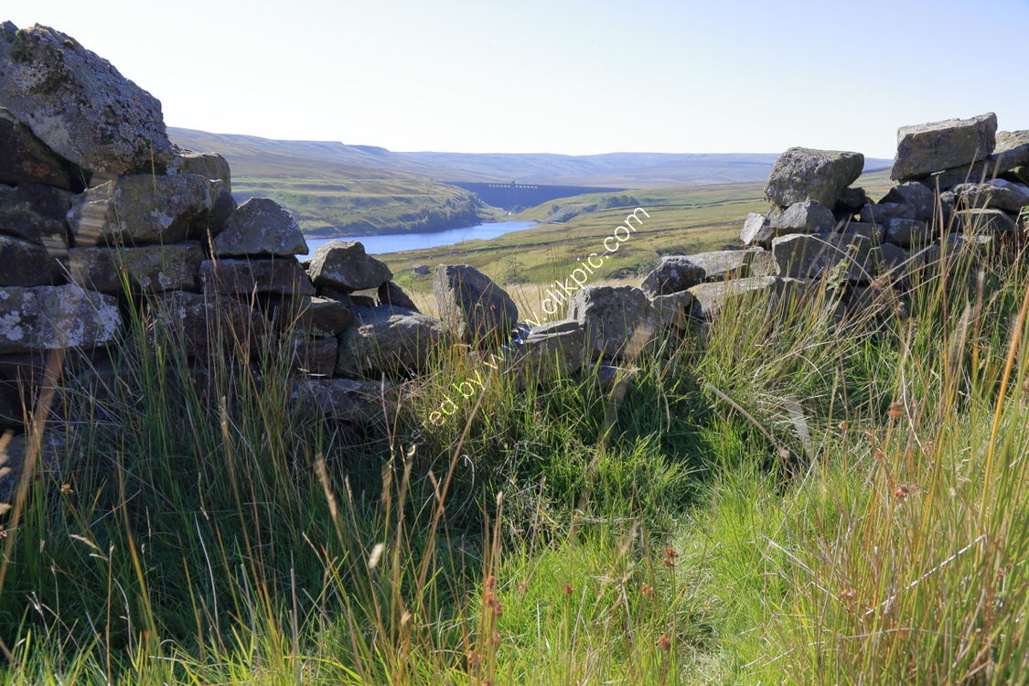 Angram Dam through a broken drystone wall at the abandoned hamlet of Lodge