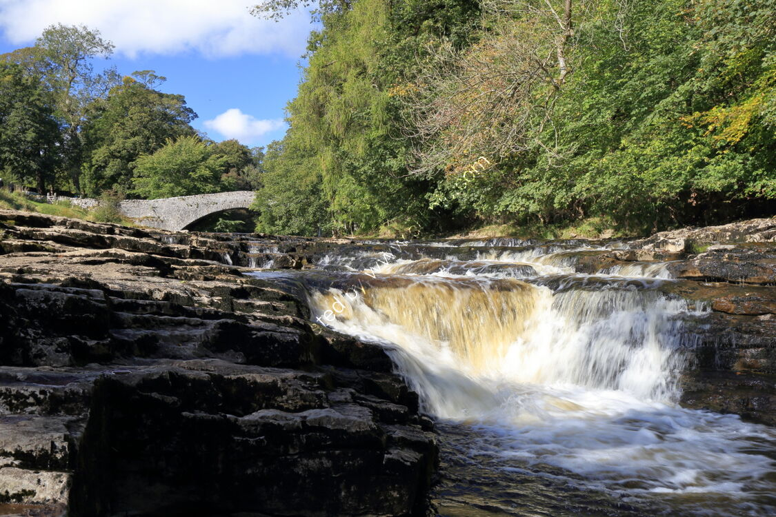 Waterfall on River Ribble at Stainforth Force, with packhorse bridge in background