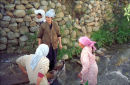 Women washing a carpet in the stream