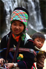 Young girl with baby by a waterfall in Sappa Vietnam