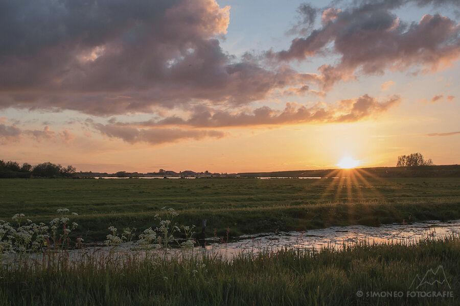 De zon zakt achter de Waterlandse Zeedijk