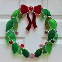A stained glass wreath made of green glass, topped with a red galss bow and decorated with glass jewels and beads