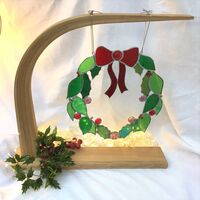 A decorative Chistmas wreath made of red and green glass with glass jewels and beads. Hung on an elegant wooden stand
