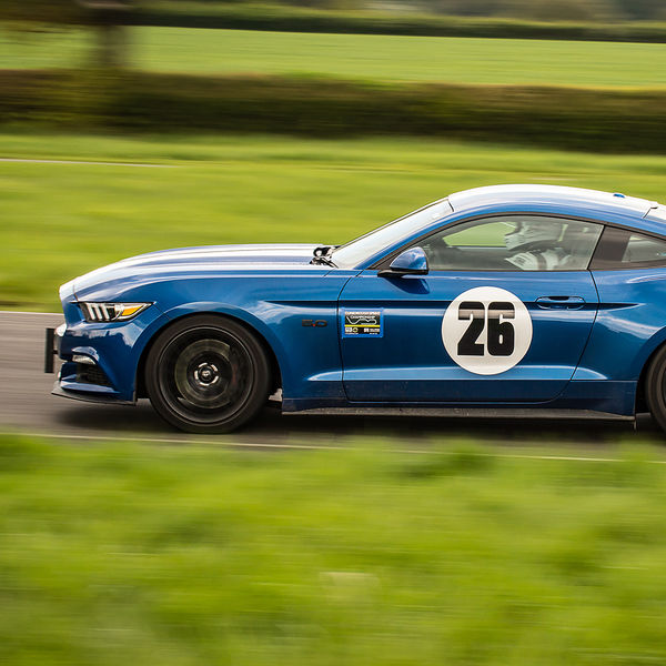 blue ford mustang full speed with panning photography