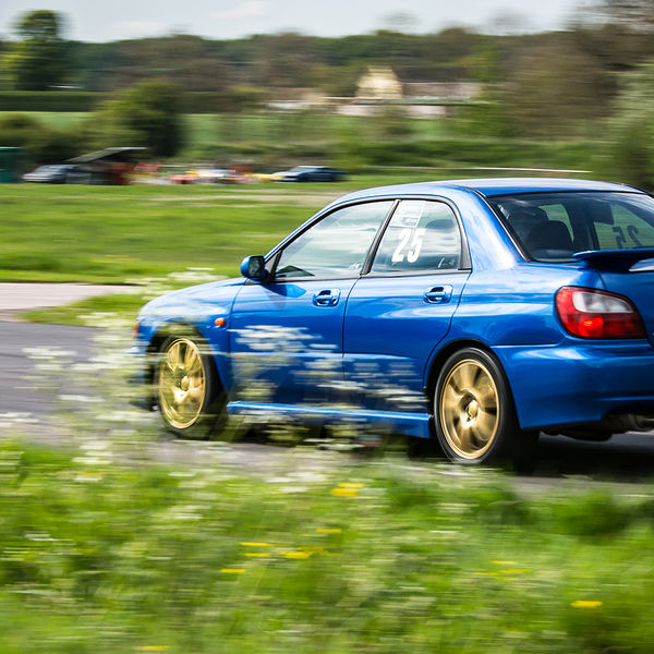 blue subaru impreza hard on the brakes at flagpole corner
