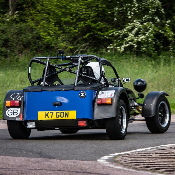 Blue Caterham 7 at speed round flag pole corner at shenstone sprint course