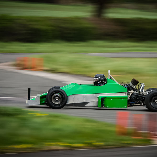 green motorcycle engined race car at speed through molehill corner at curborough sprint track