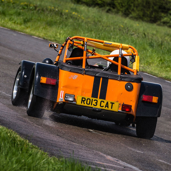 Orange Lotus 7 Caterham Westfield opposite lock in rain at Curborough Sprint Course
