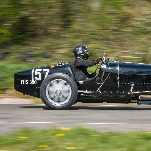 black vintage bugatti at speed through curborough flagpole corner
