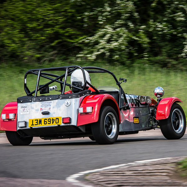 Red Caterham 7 at speed round flag pole corner at shenstone sprint course
