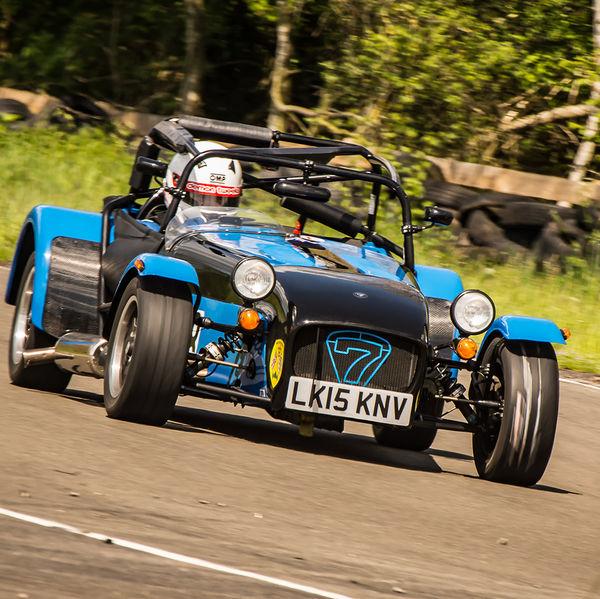 bright blue caterham 7 at speed through curborough sprint course mole hill corner