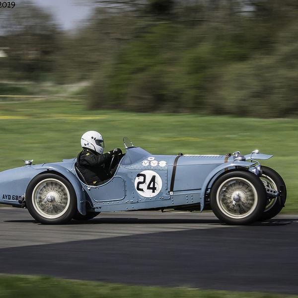 pale blue vintage sports car speeding along curborough sprint track