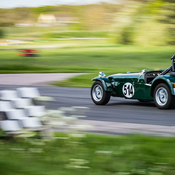 Green Caterham 7 at speed past the chequered flag at shenstone sprint course