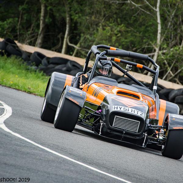 orange and black lotus 7 caterham westfield at speed through molehill corner at curborough sprint track