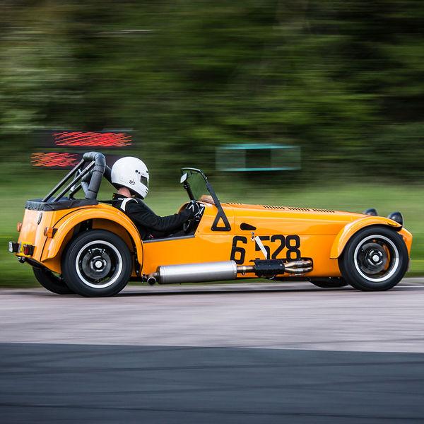 Orange Caterham 7 at speed through flag pole corner at shenstone sprint course