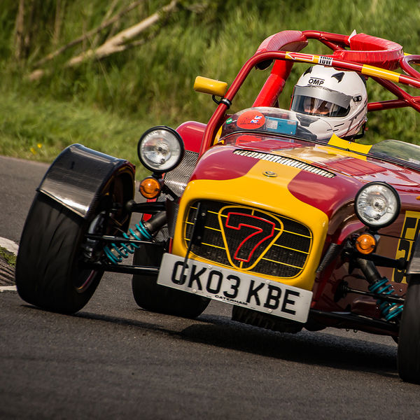 yellow and red caterham 7 rounding the fradley hairpin corner at curborough sprint track