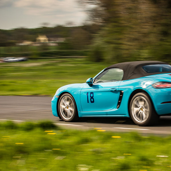 bright blue porsche 911 cabrio braking hard at flagpole corner
