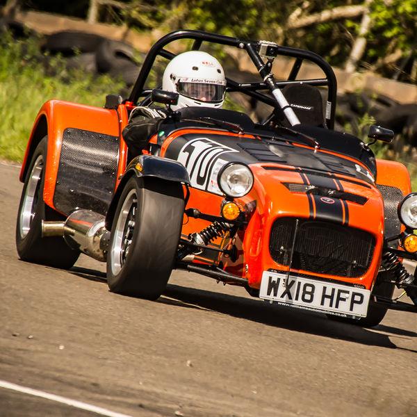 orange caterham 7 at speed through curborough sprint course mole hill corner