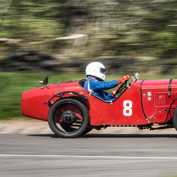 red vintage racing car taking curborough flagpole corner at speed