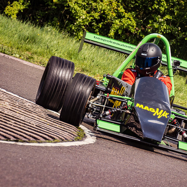 green racing car speeding round curborough hairpin